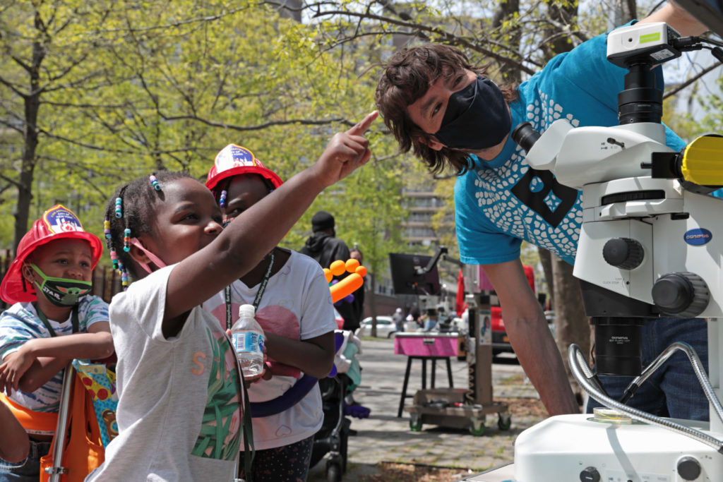 Outside with 3 students standing on the left facing a microscope with an adult. All are wearing t-shirts. One student is pointing towards the microscope. Another microscope science station is in the background.